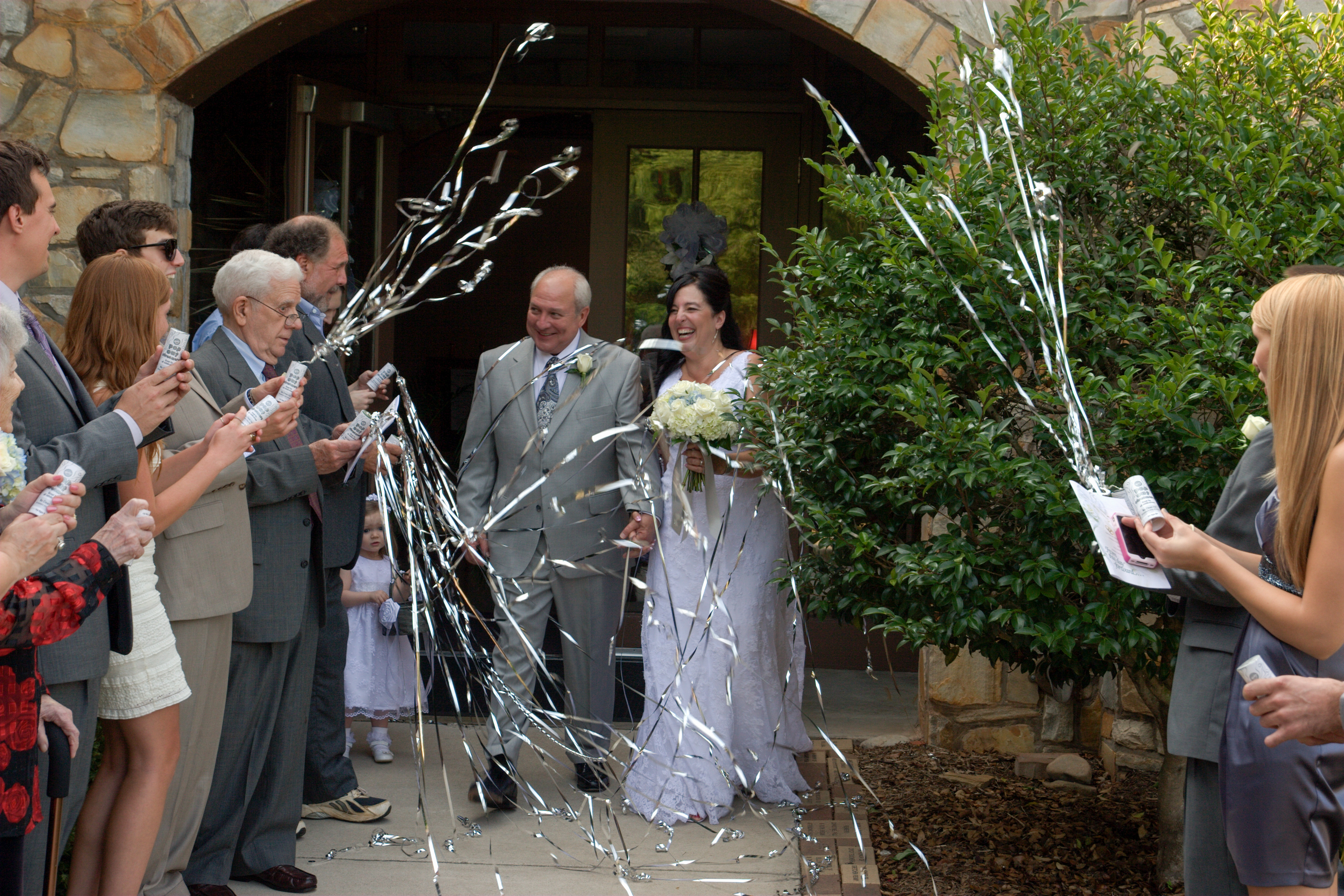 Wedding couple exit through streamers
