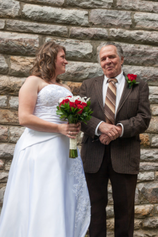 Bride and father with stone wall background