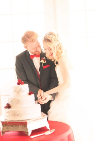 red winter wedding couple cut cake