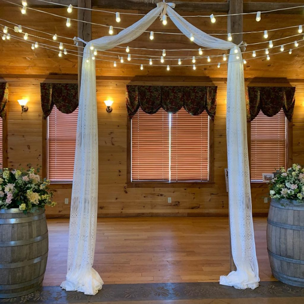 String lighting above a fabric wedding altar frame